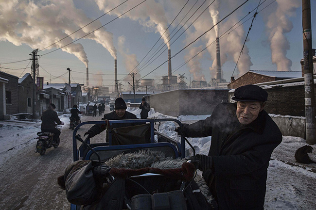 China's Coal Addiction - Kevin Frayer - Smoke billows from stacks as men push a tricycle through a neighborhood next to a coal-fired power plant in northern Shanxi province.