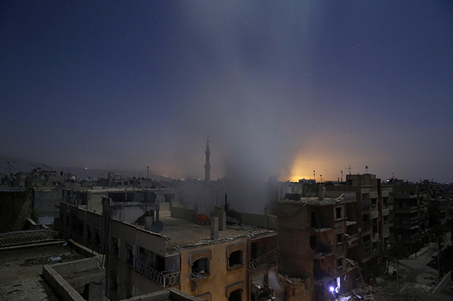 Aftermath of Airstrikes in Syria - Sameer Al-Doumy - Smoke billows from a building in Douma.